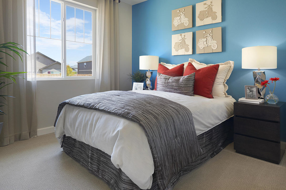 A bedroom featuring a blue wall with motorcycle artwork and a grey bedspread.