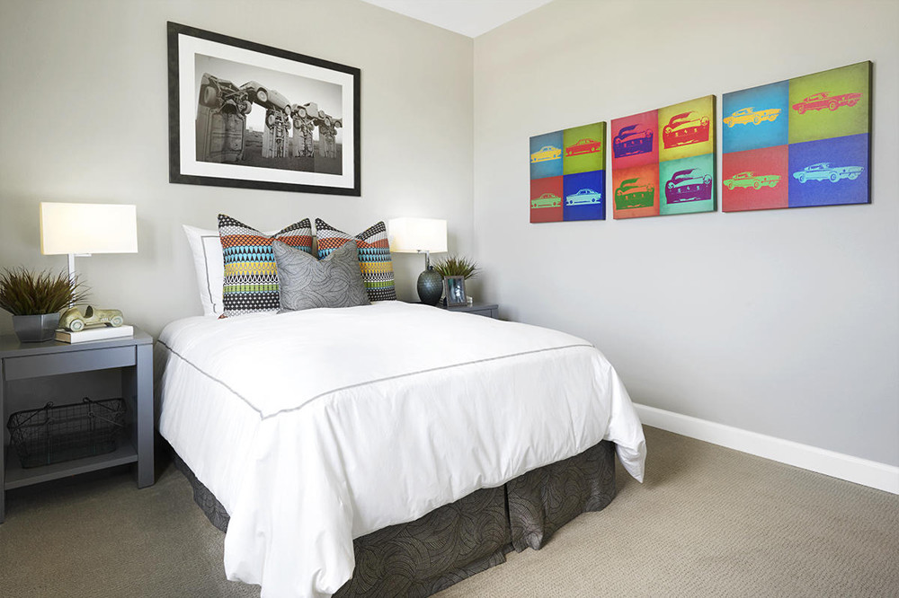 A new bedroom with a white bed featuring colorful throw pillows ans colorful artwork on the walls.