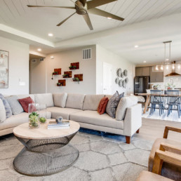 A very large open concept great room with large sectional, leading into the dining room and a modern kitchen.