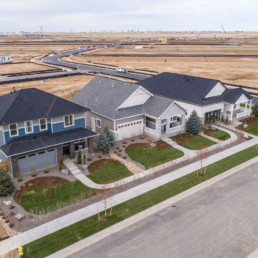 An aerial view of 3 new houses in a new neighborhood.