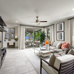 The living room of a beautiful new homes, with a view out to the patio.