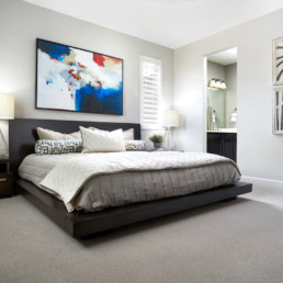 A large king size bed in a master bedroom with a beautiful colorful painting on the wall.