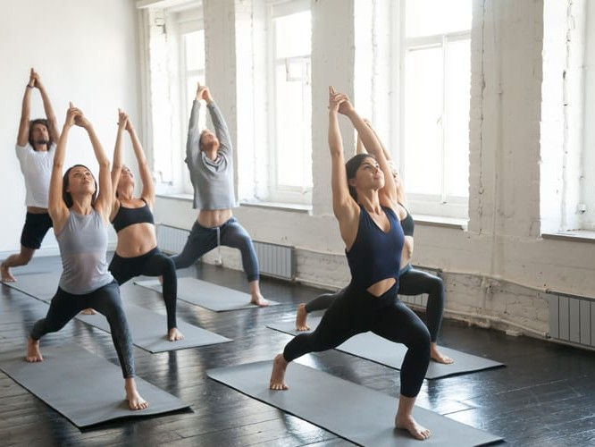 A group of six young adults practicing yoga in a studio next to bright windows.